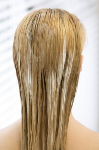 Female young woman coloring her hair applying color cream
