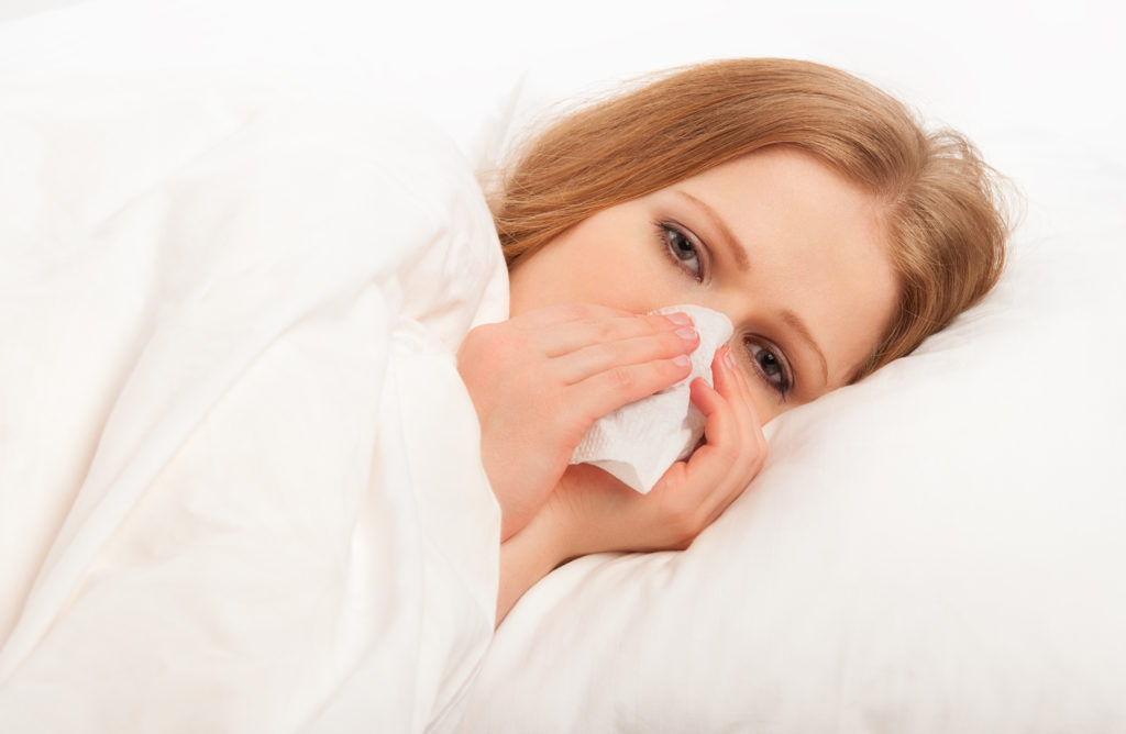 ill sick girl sneezes and blows her nose into a handkerchief in bed