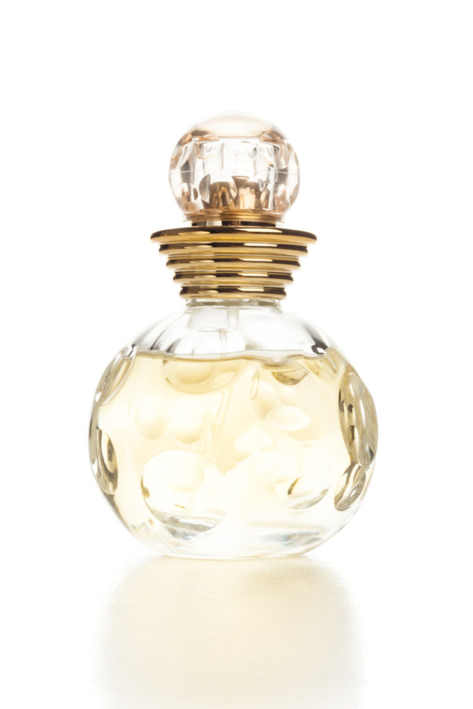 back lit yellow womens perfume bottle on white