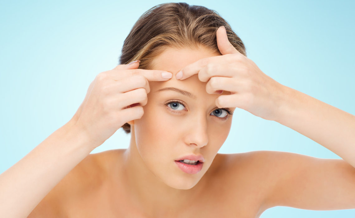 beauty, people, skincare and health concept - young woman squeezing pimple on her face over blue background