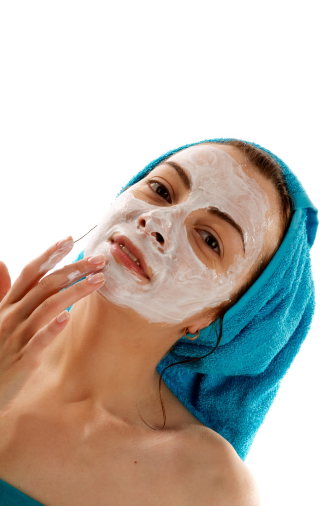Young Women in Blue Towel on her Head Applying White Facial Skincare Mask closeup on white background