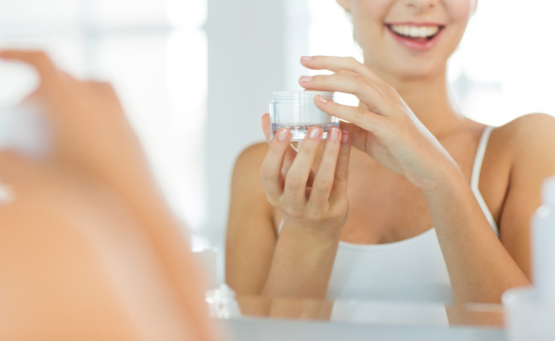 beauty, skin care and people concept - close up of smiling young woman with face cream mirror reflection at home bathroom