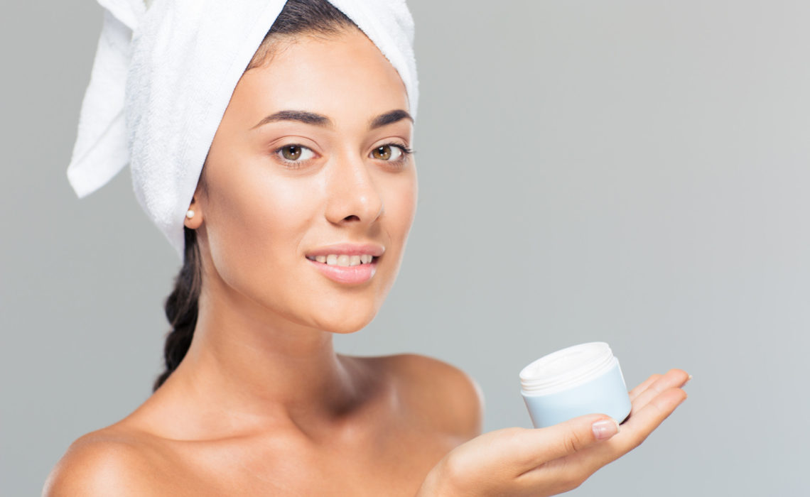 Portrait of a smiling cute woman with towel on head holding cream jar over gray background and looking at camera