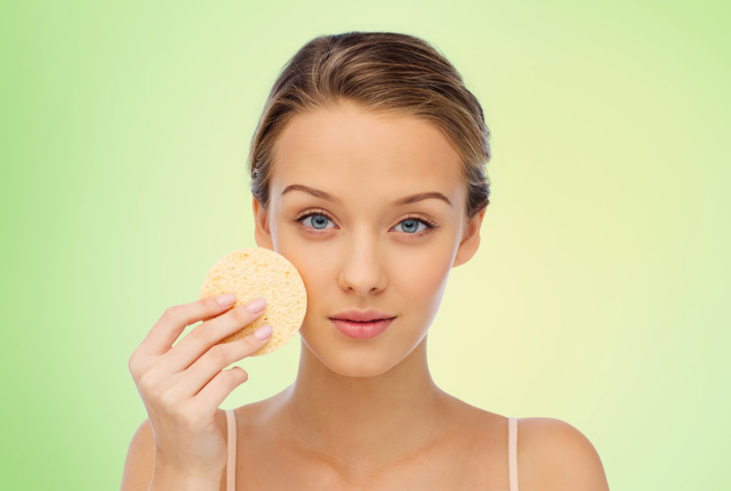 beauty, people and skincare concept - young woman cleaning face with exfoliating sponge over green background