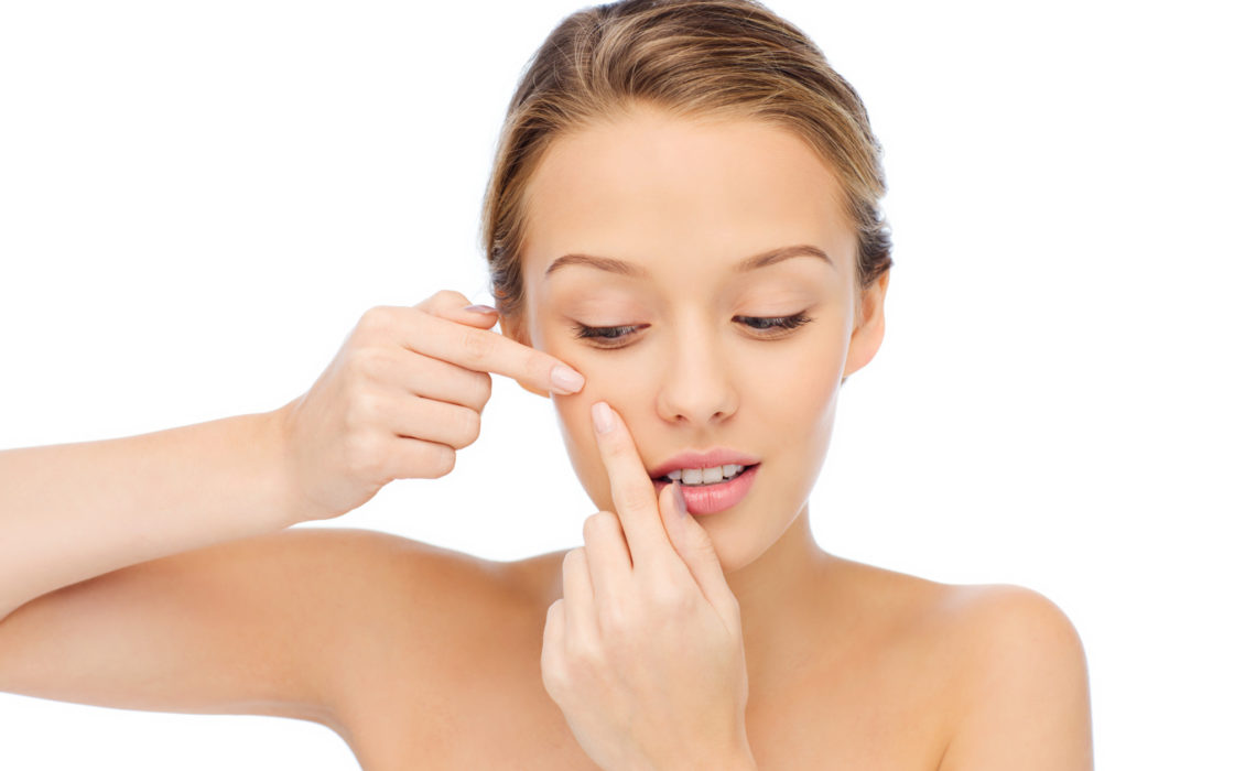 beauty, people, skincare and health concept - young woman squeezing pimple on her face