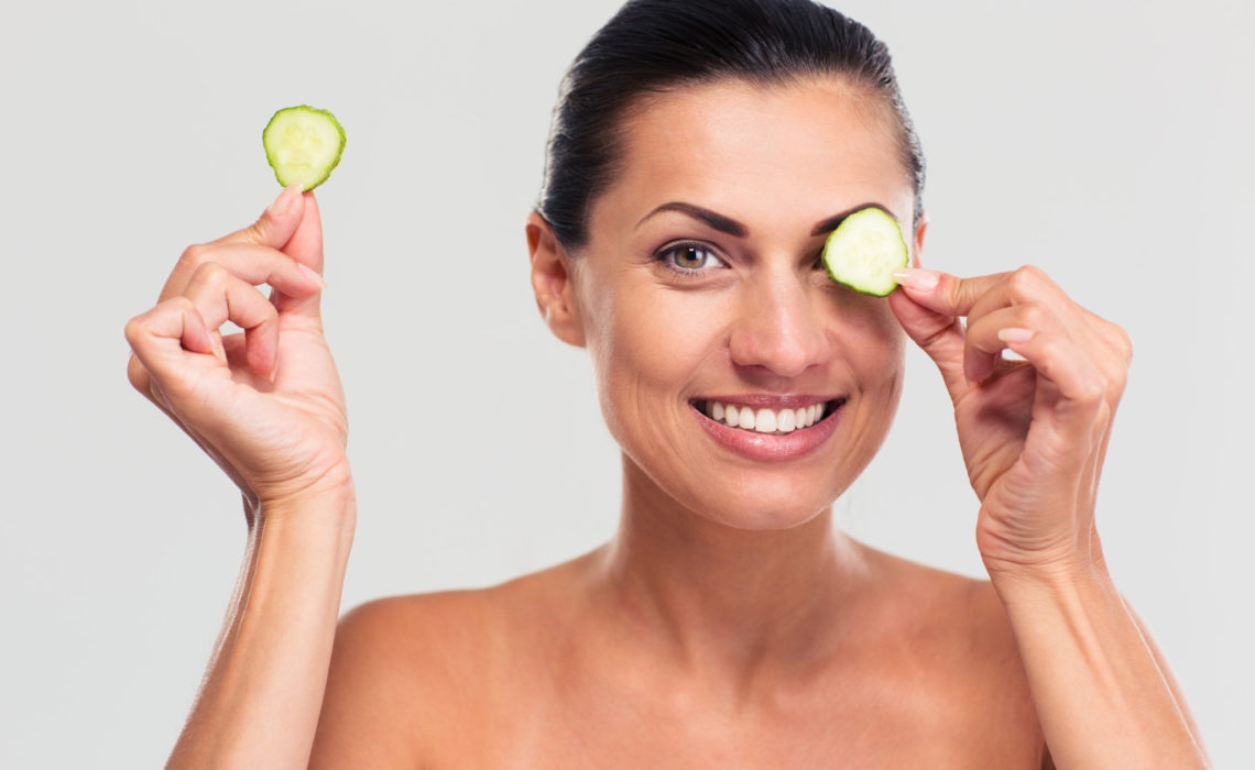 Spa concept. Happy woman covering her eye with cucumber and looking at camera isolated on a white background