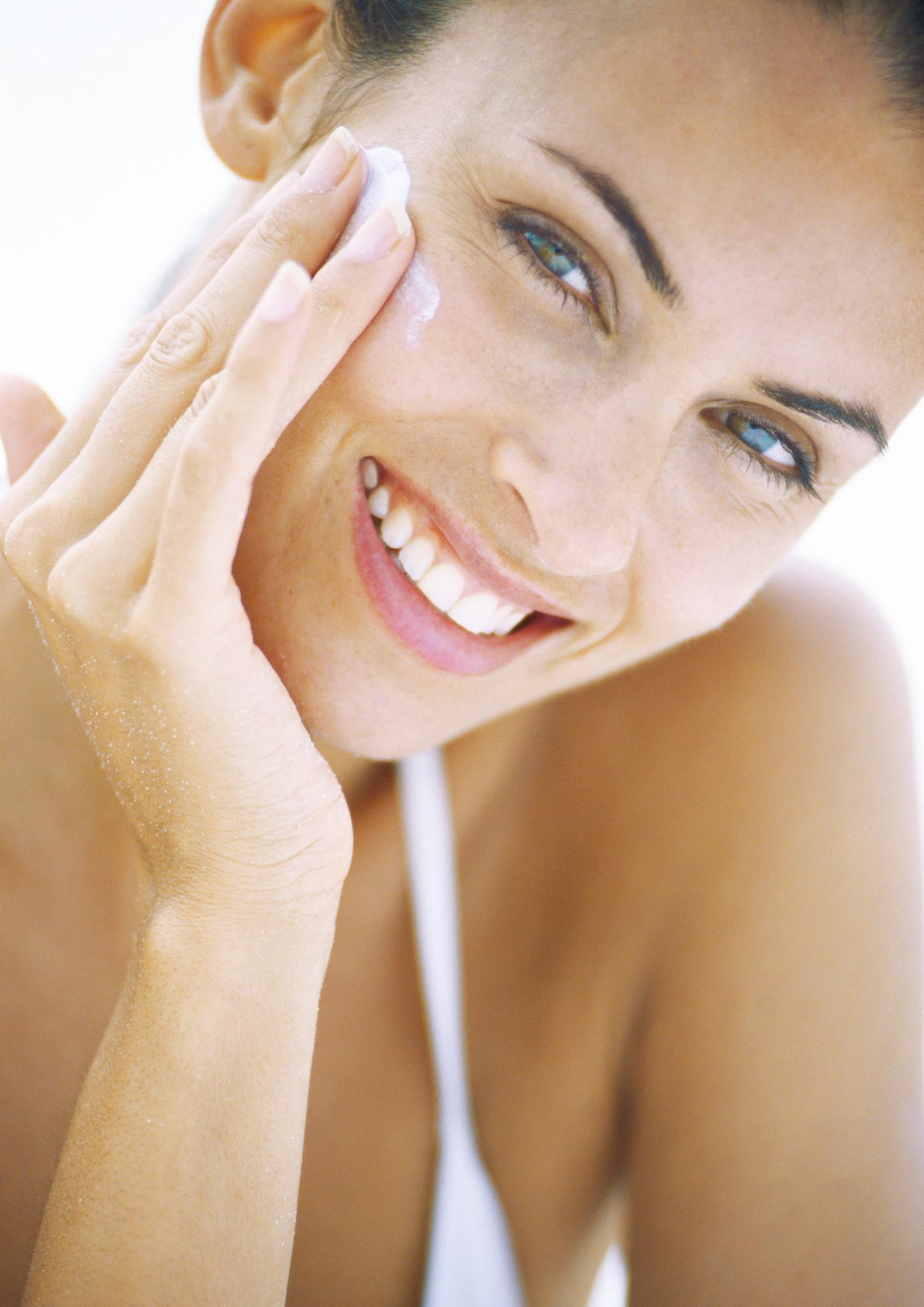©Alix Minde/AltoPress/Maxppp ; Woman applying sunscreen to face, close-up