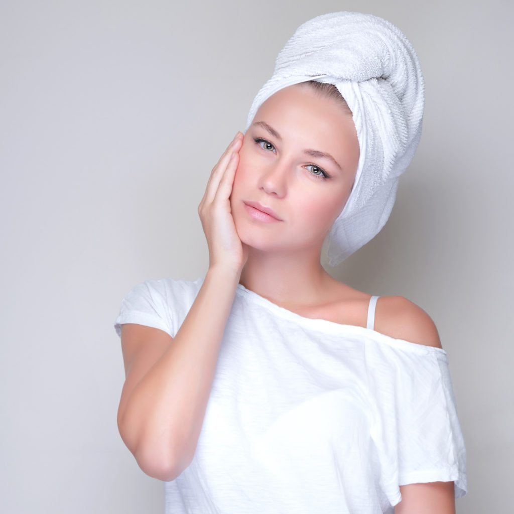 Closeup portrait of beautiful young woman with towel on head isolated on gray background, enjoying day spa, beauty treatment concept