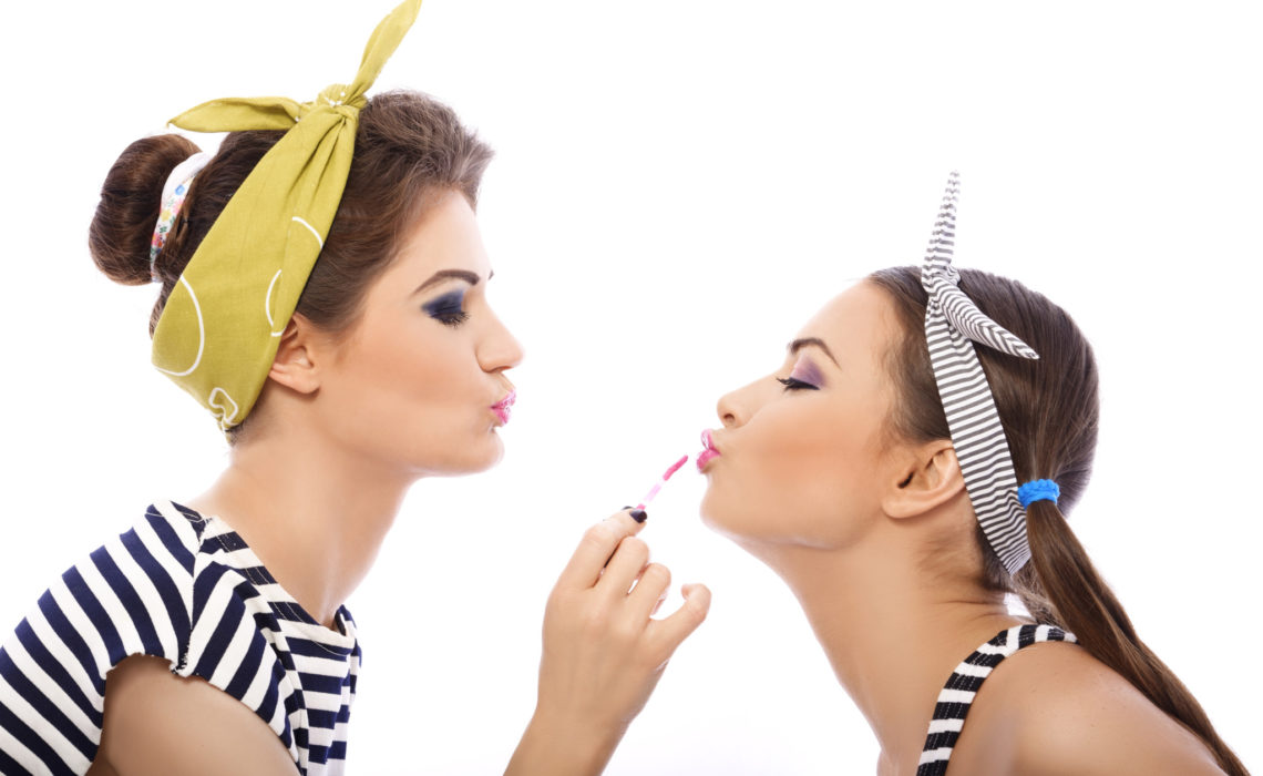 Girls paint their lips to each other. They wear funny scarves and striped shirts.
