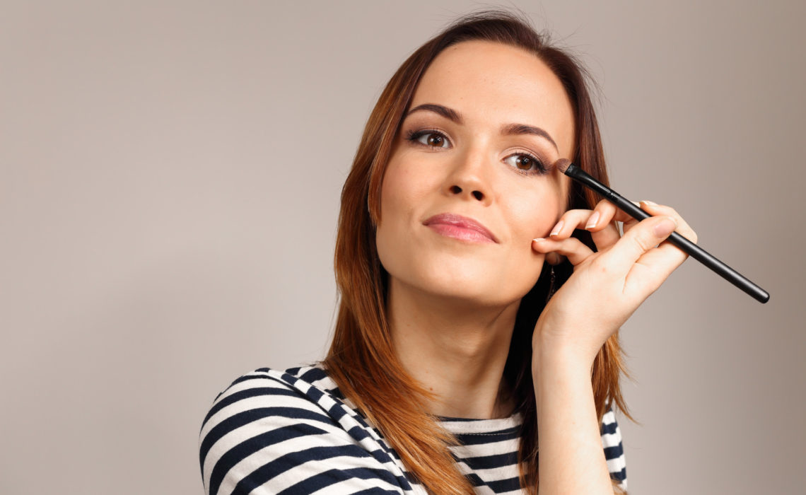 Applying eye makeup products on woman's face. Eyes Makeup. Eyes shadows. Eye shadow brush. Perfect face makeup process.