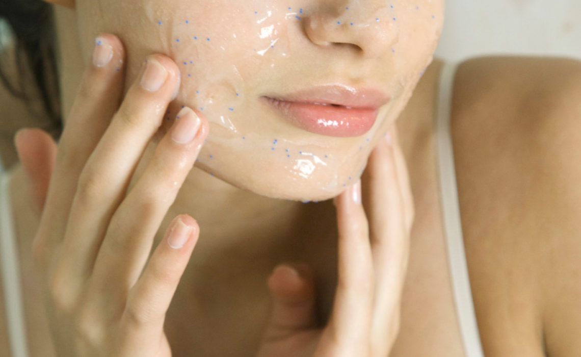 Young woman putting exfoliant mask on face, smiling at camera