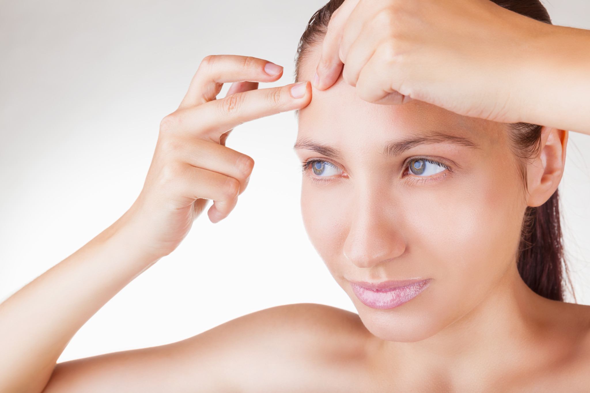 Young woman squeezing pimple on her forehead on white background
