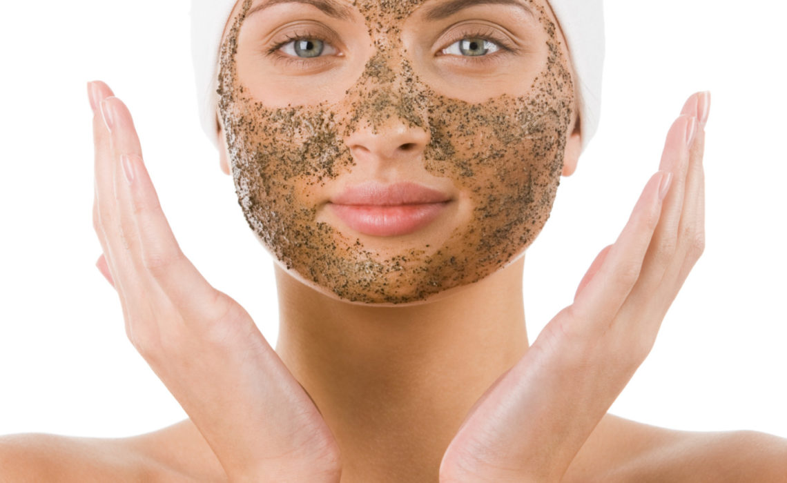 Beautiful woman with purifying facial mask keeping her palms by her face
