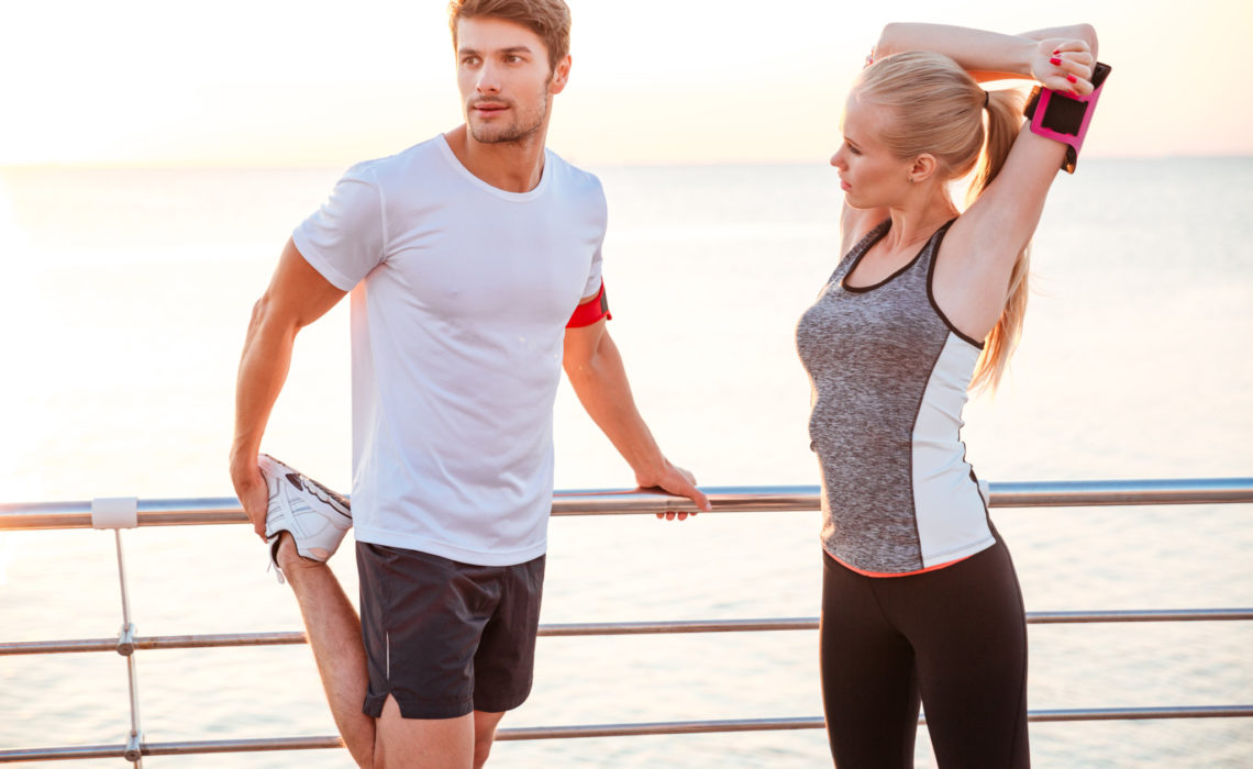 Athletic young couple stretching out after running at the beach pier