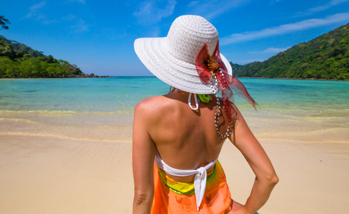 Closeup of back beautiful and tanned woman with sarong, bikini and white wide-brimmed hat, looks tropical beach of Koh Surin Nuea, North Surin Island National Park, Phang Nga, Andaman Sea, Thailand
