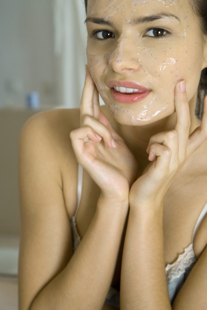 Young woman applying facial mask, looking at camera, cropped view