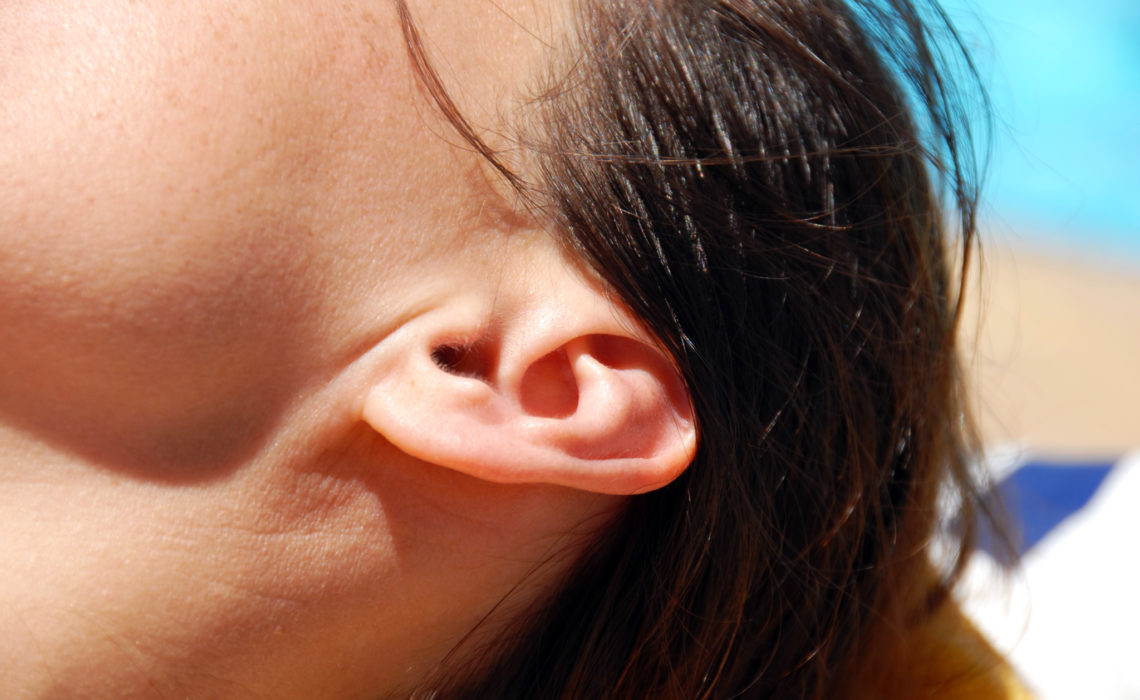 brunette female ear closeup on sunlight outdoor