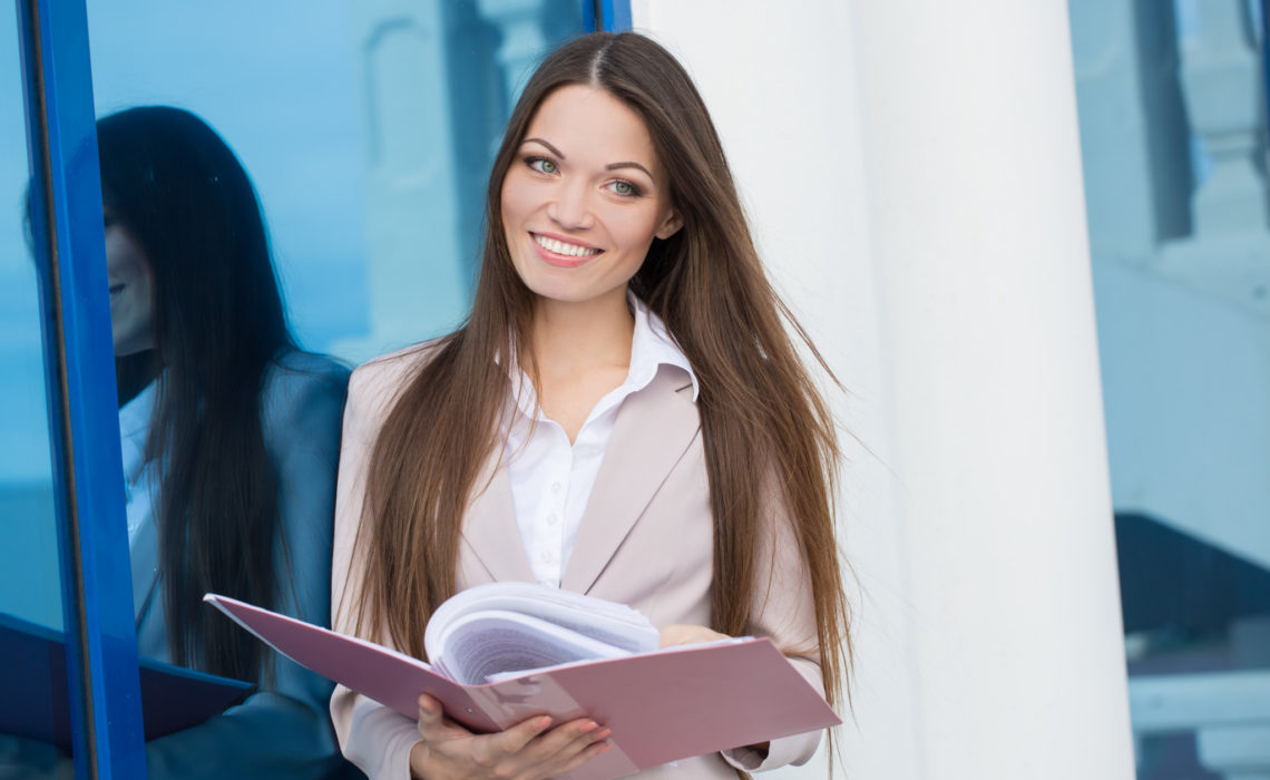 Young beautiful businesswoman with folder in hands