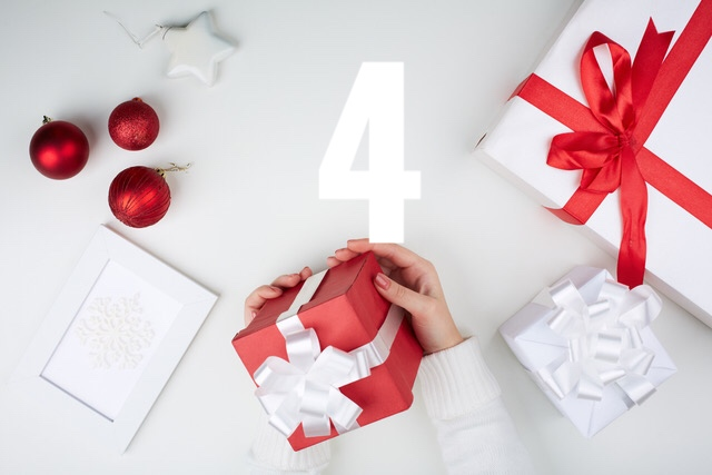 Image of giftbox held by female surrounded by other xmas symbols