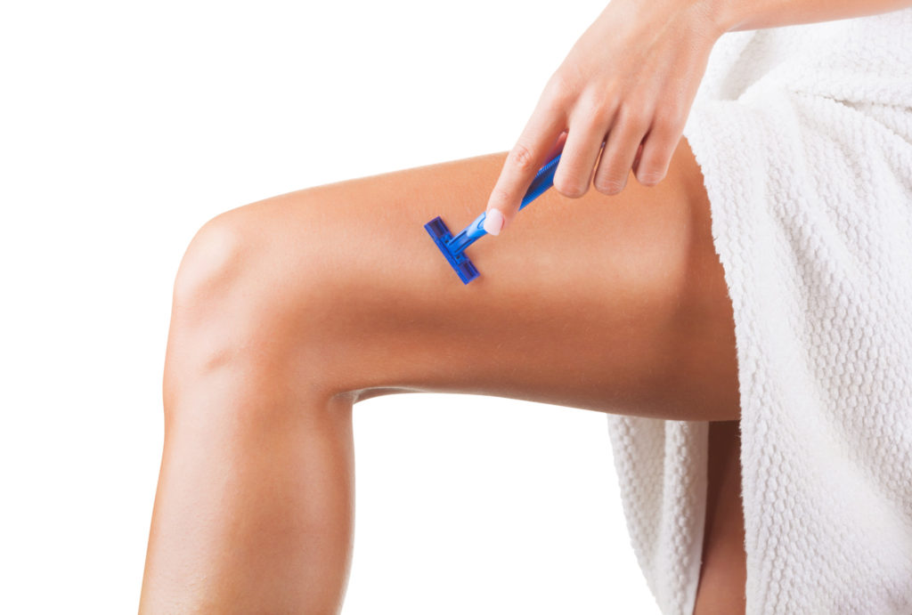 Close-up of a young woman shaving legs isolated on white background