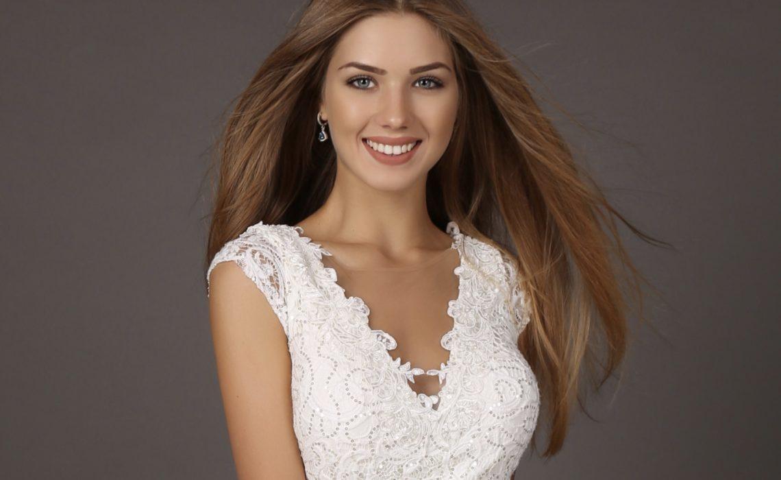 fashion studio photo of beautiful smiling woman with long hair wears luxurious sequin dress