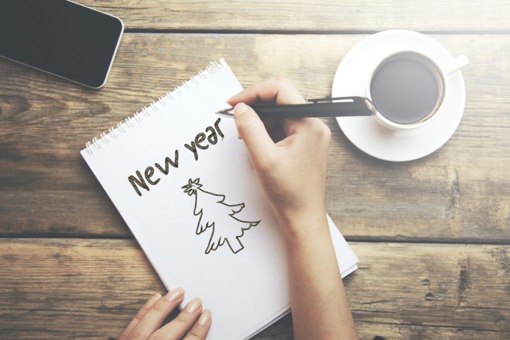 woman written new year text on notepad