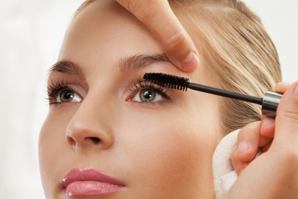 Close-up of separating and curling lashes process with mascara brush