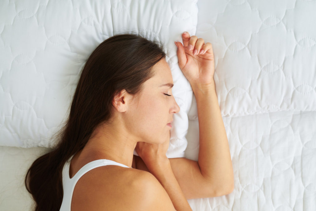Top view of young beautiful woman sleeping lying on the side in the bed early in the morning
