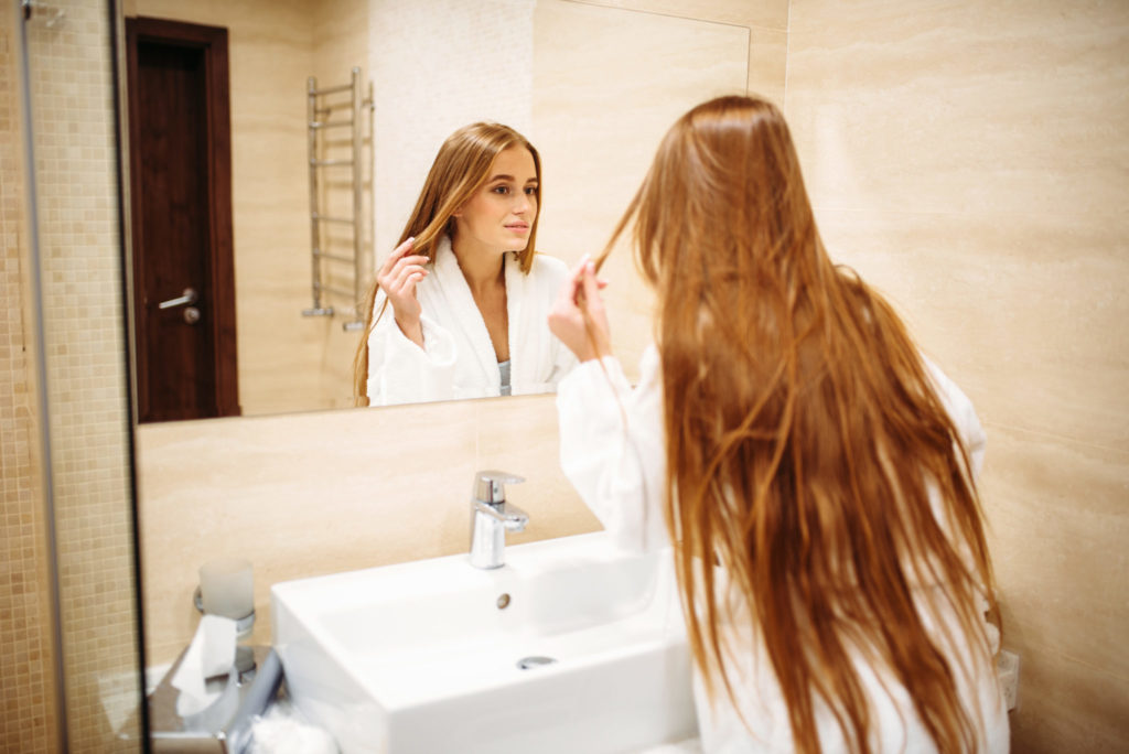 Beautiful woman in bathrobe against mirror in bathroom, morning hygiene, beauty and hair care