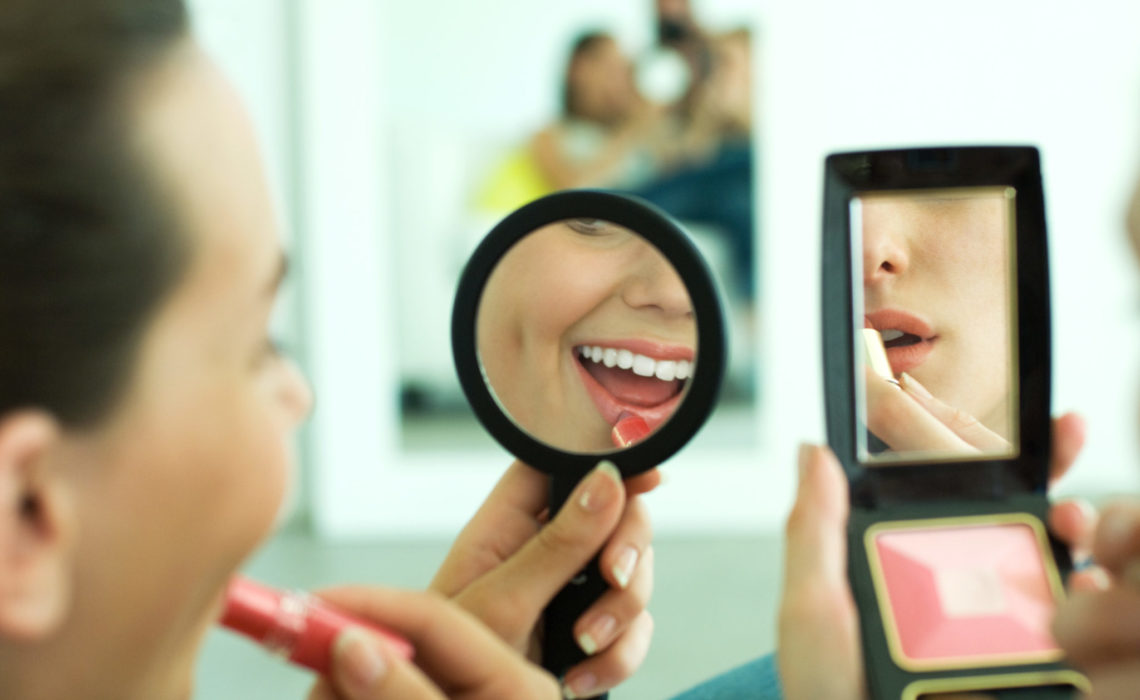 Two young friends applying lipstick, looking at selves in hand mirrors, cropped view