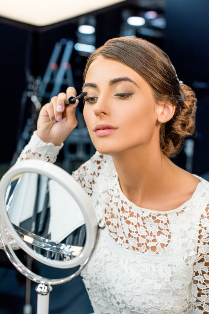 portrait of young woman looking in mirror and applying mascara in beauty studio