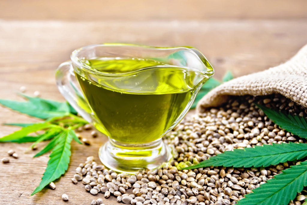Hemp oil in a glass sauce-pot with grain in a bag, leaves and stalks of cannabis on a wooden board background