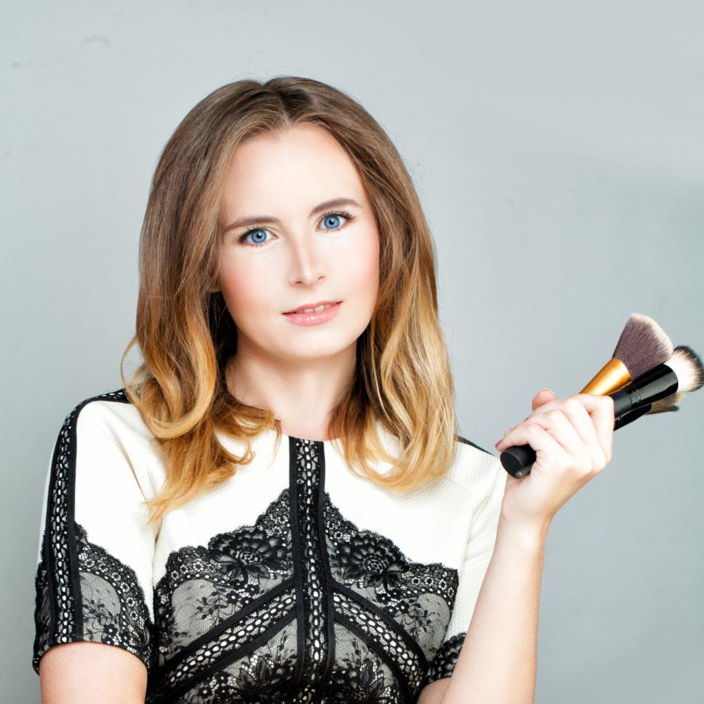 Elegant Woman Makeup Artist holding Makeup Brushes