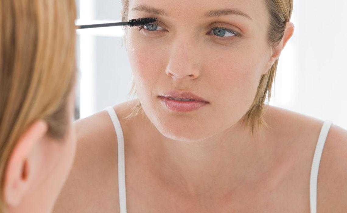 A woman applying mascara