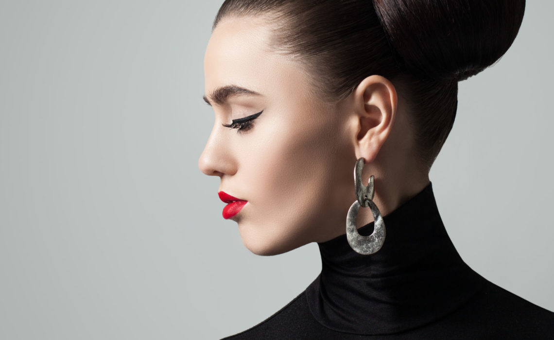 Perfect Young Woman with Hair Bun Hairstyle and Eyeliner Make up. Cute Female Model wearing Black Roll Neck Jersey