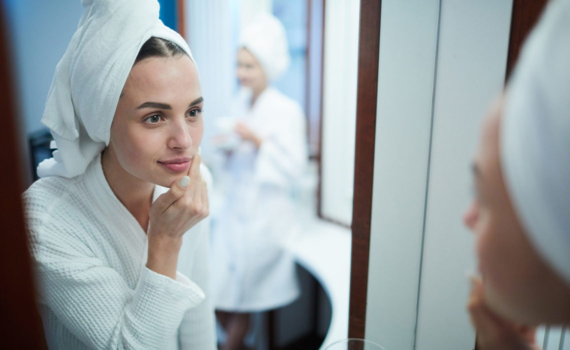 Young woman with soft towel on her head looking in mirror while taking care of her face