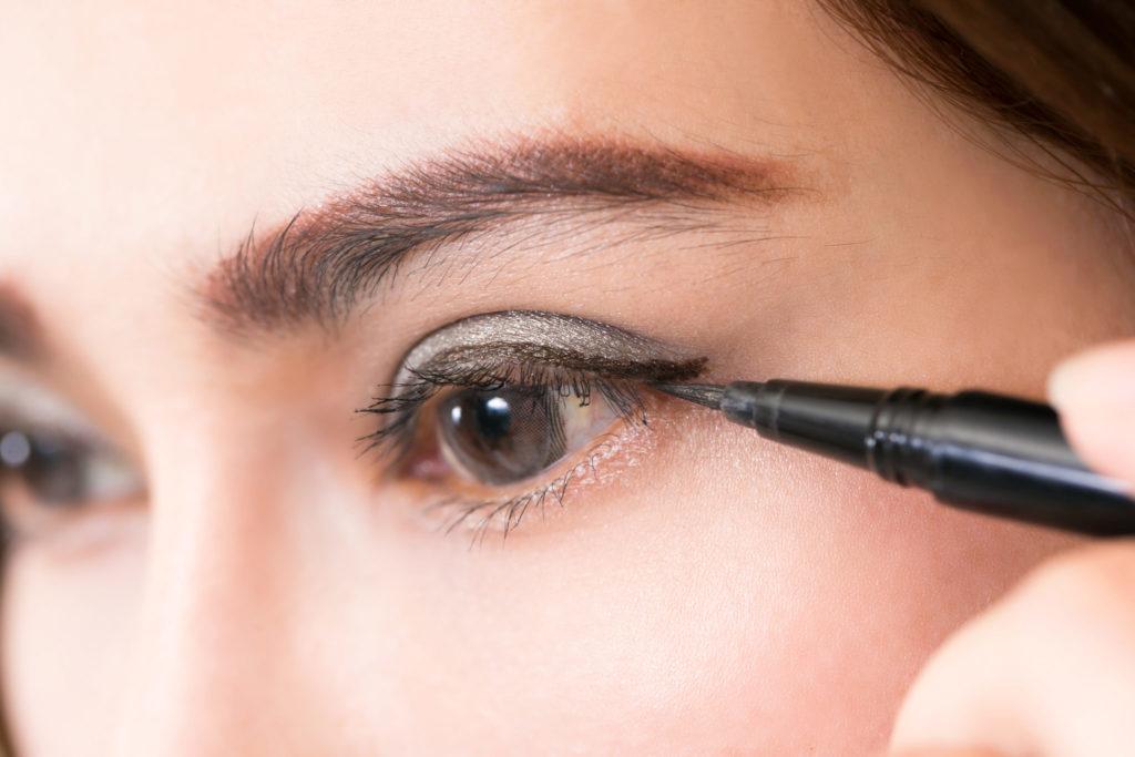 Beautiful woman make-up with black eyeliner.