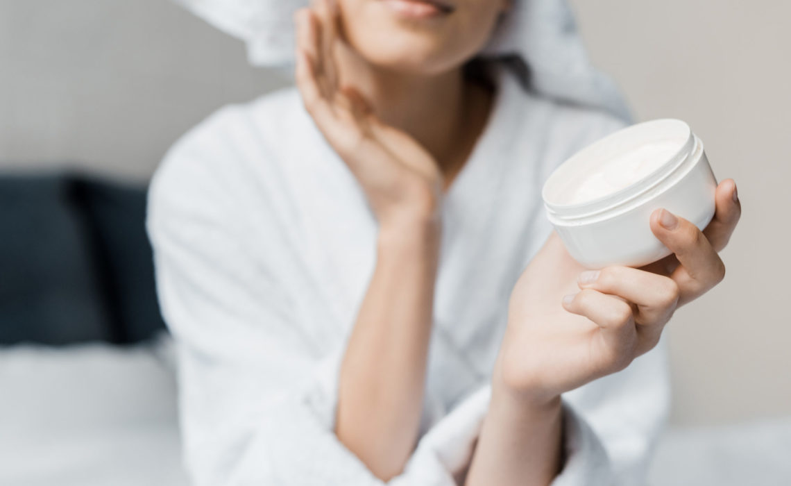 cropped view of girl applying cosmetic cream on face