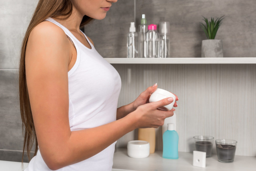 Cropped image of woman opening cream in a bathroom