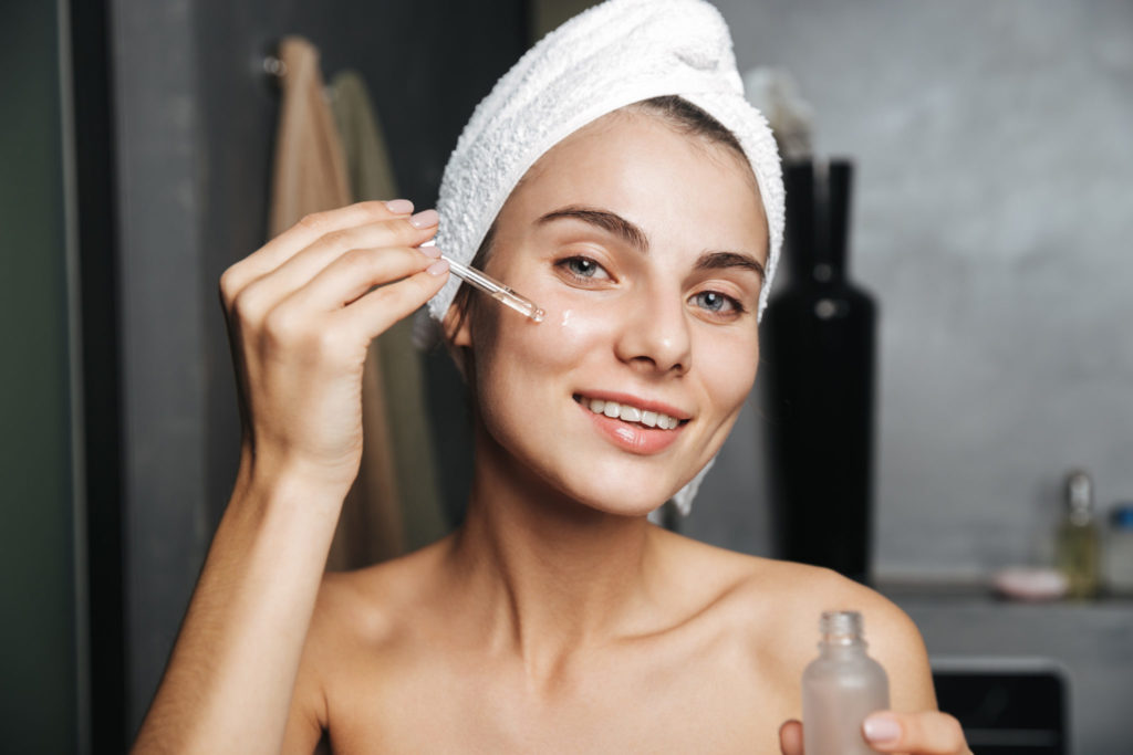 Photo of caucasian woman with towel on head applying cosmetic oil on her face while standing in bathroom
