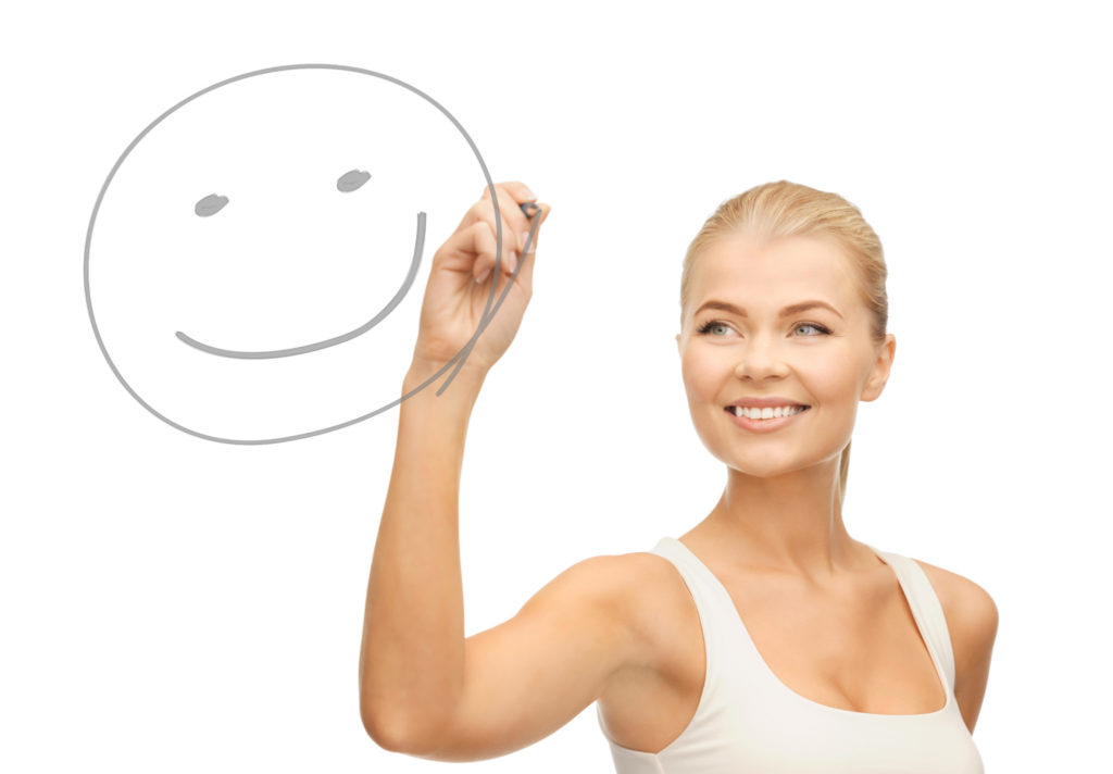 smiling woman in white shirt drawing happy smile on glass