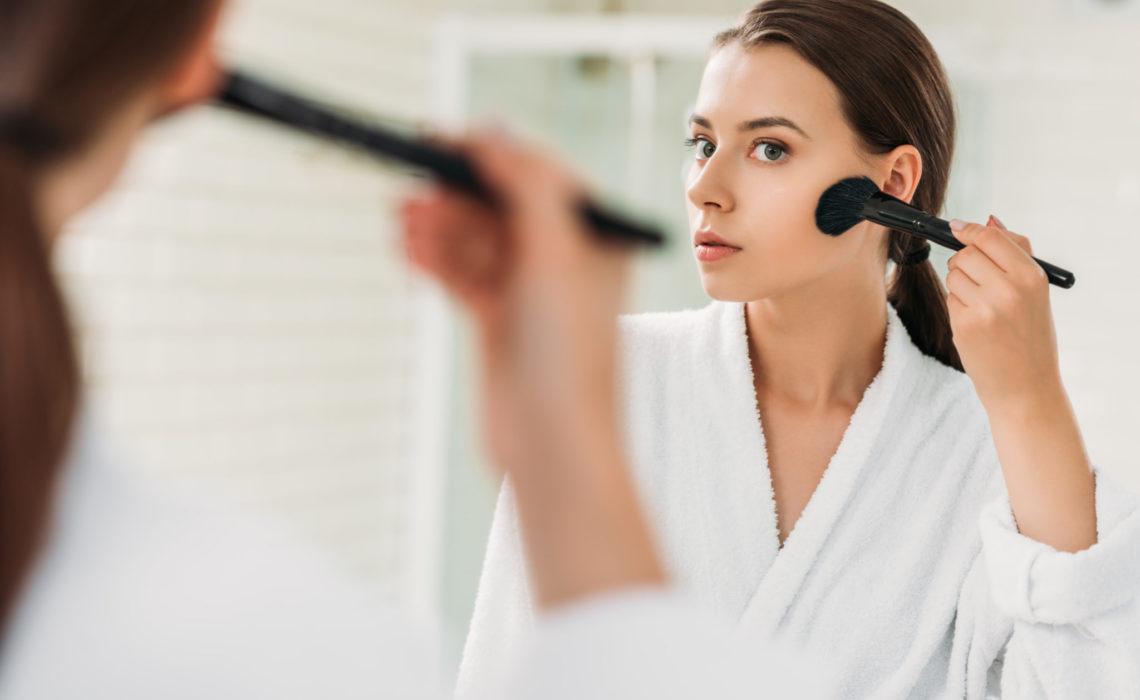 beautiful brunette girl in bathrobe looking at mirror and applying powder