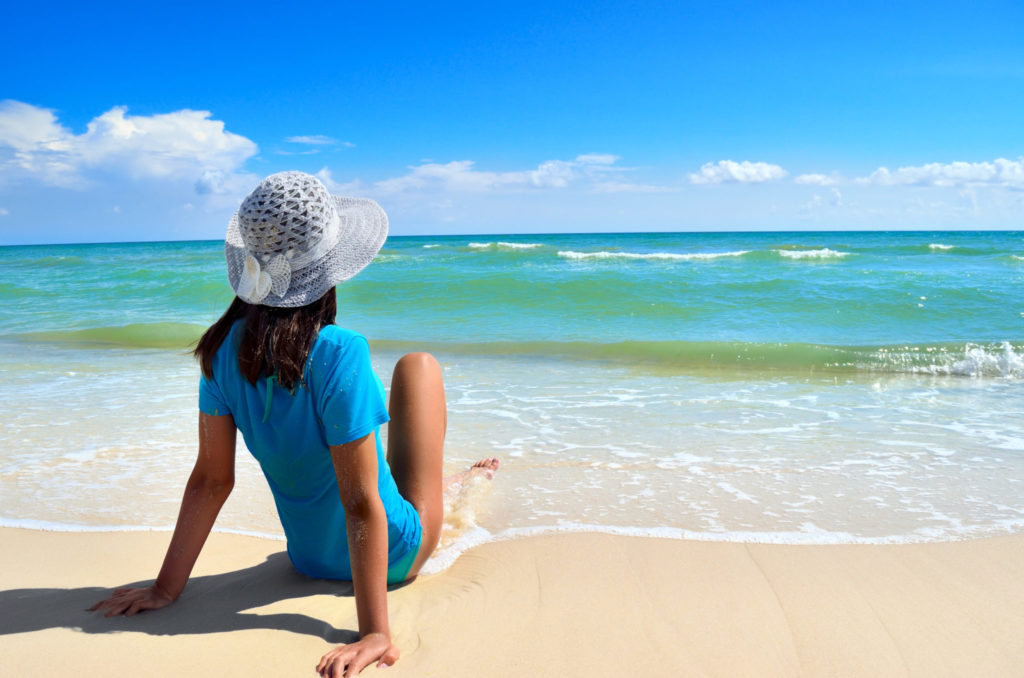 Young girl in a white hat on the sea beach. Clean, sandy beach against the blue sea.