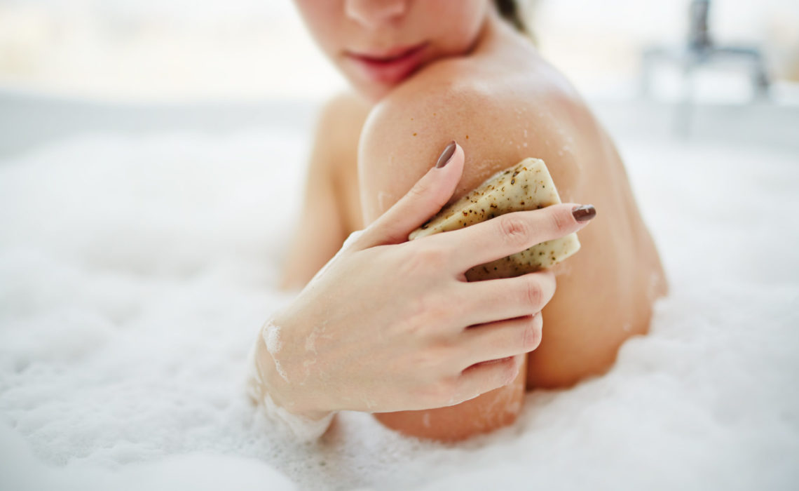 Young woman scrubbing her skin in a bath