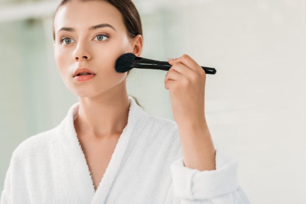 beautiful girl in bathrobe applying bronzer with brush