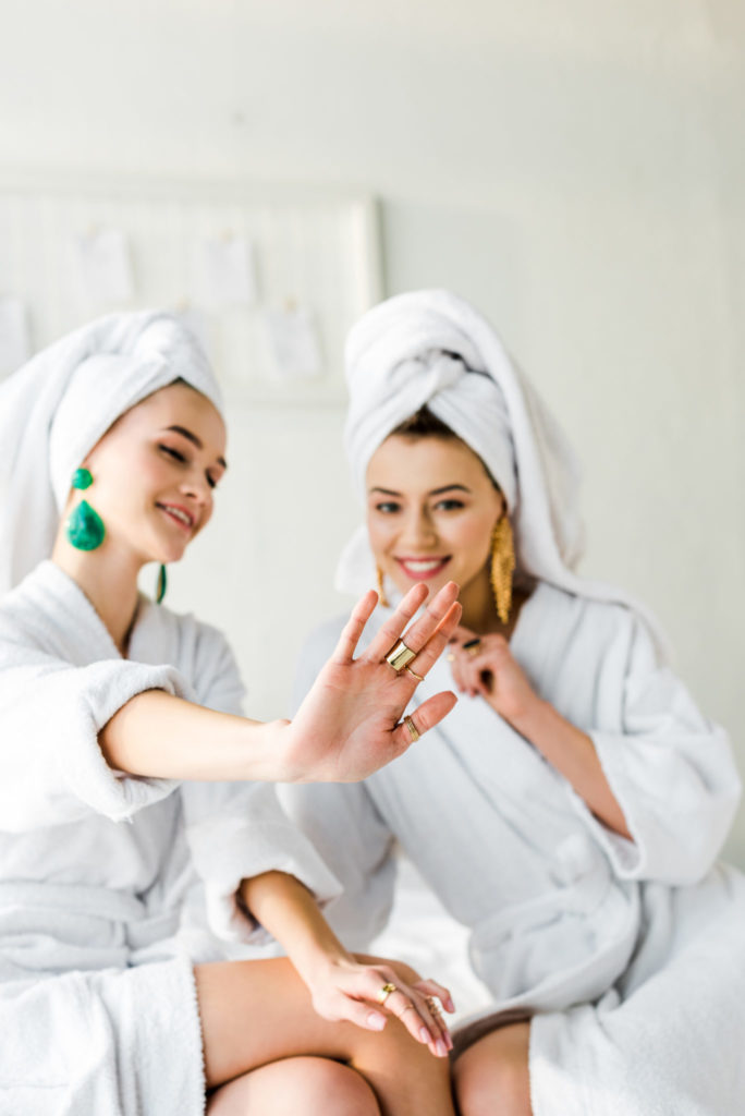 selective focus of stylish girls in bathrobes and towels on heads looking at rings on hand