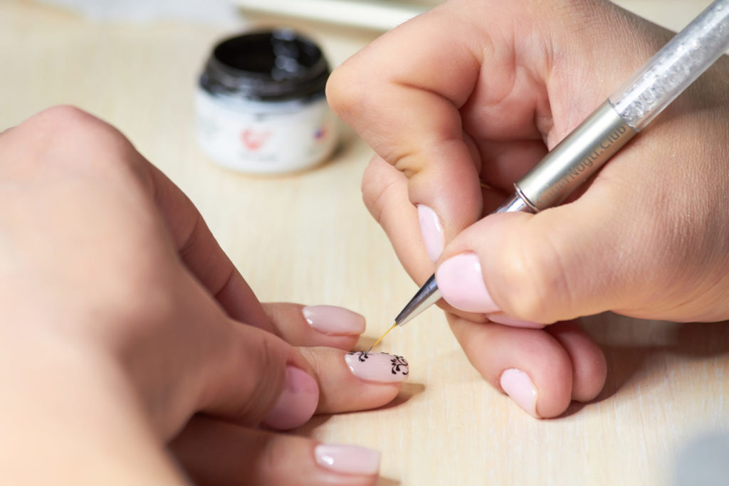 The drawing process on female nails. Female manicurist hand putting black lace on nude nail polish in beauty salon. Female nails manicure.