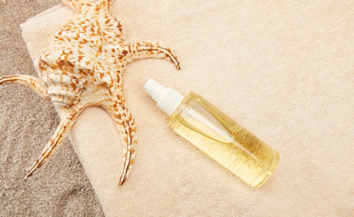 top view of arranged pile of towels, seashell and tanning oil on sand