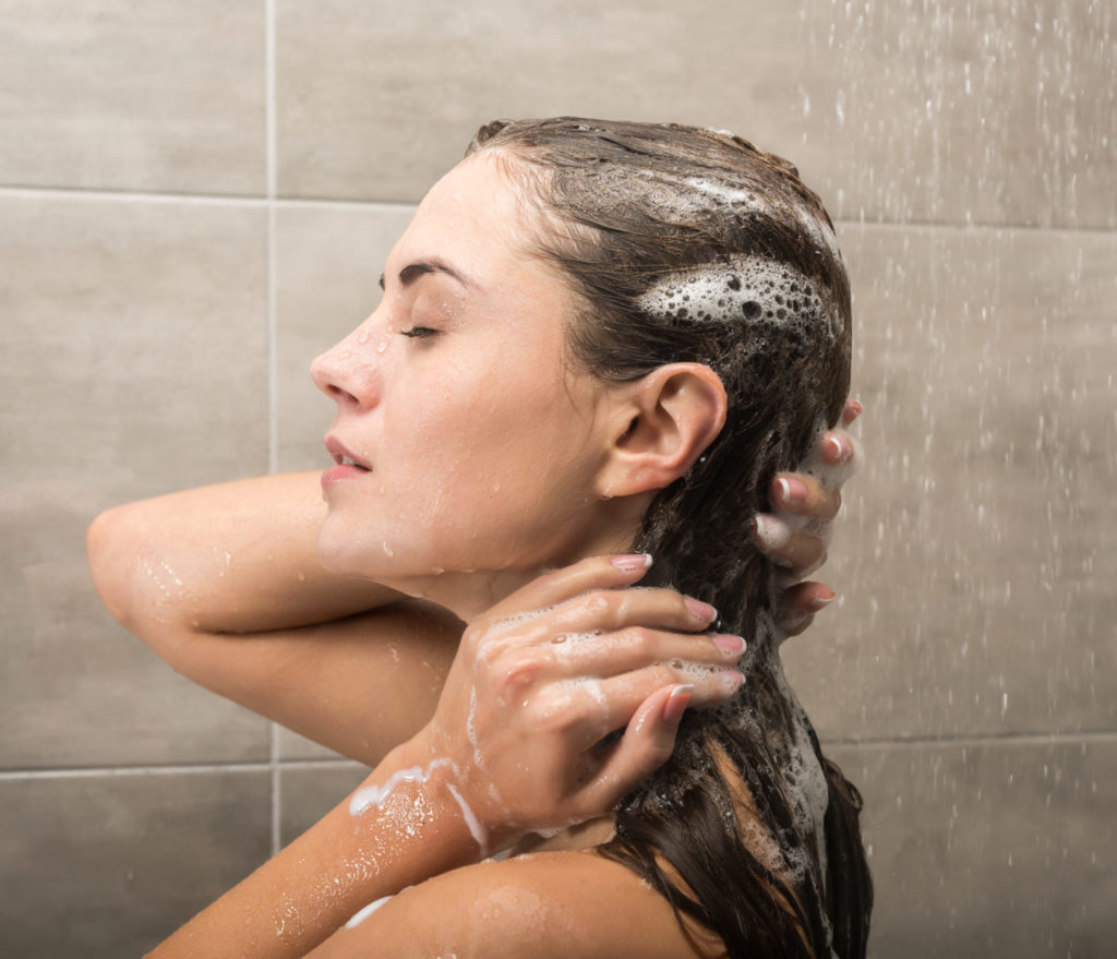 Side view of girl washing hair with shampoo in the shower