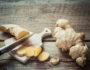 Ginger root on cutting board on rustic wooden kitchen table. Selective focus.